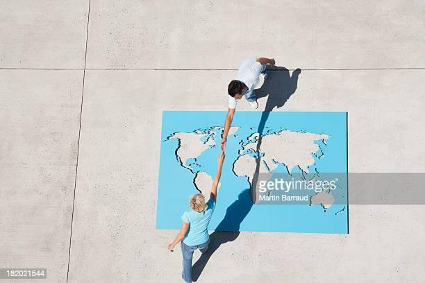 Vista aérea de hombre y mujer estrechándose las manos arriba mundo