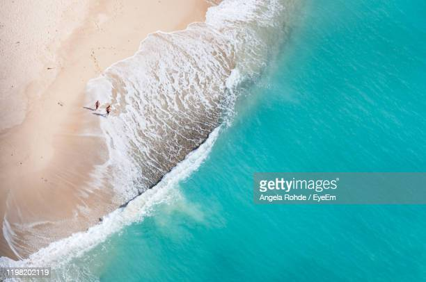 aerial view of man and woman walking at beach - antigua & barbuda stock pictures, royalty-free photos & images