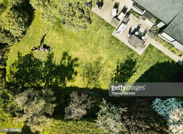 aerial view of man cutting grass in backyard of home - lawn stock pictures, royalty-free photos & images