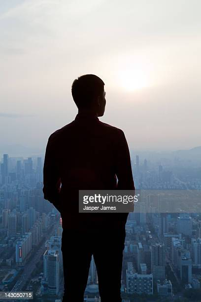 aerial view of man looking out to shenzen - silhouet stockfoto's en -beelden