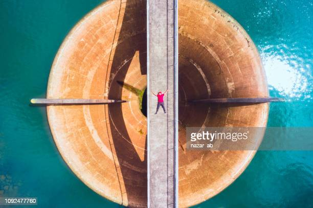 Aerial view of man lying on a bridge over spillway.