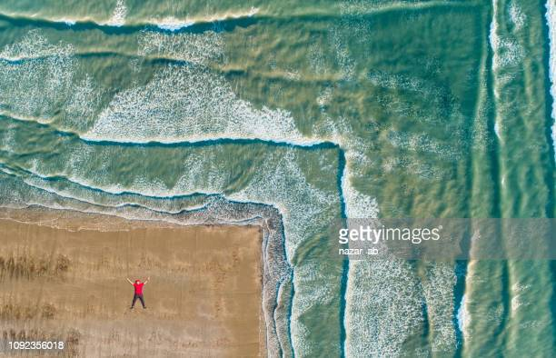 aerial view of man lying on beach. - wellington new zealand stock photos and pictures