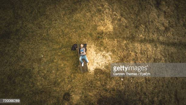 Aerial View Of Man Lying On Bench At Grassy Field