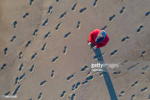 aerial view of man piloting a drone on tropical beach - footprint stock pictures, royalty-free photos & images