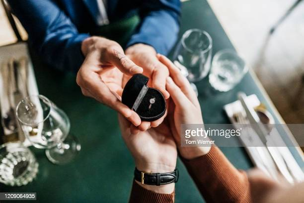 aerial view of man presenting girlfriend with engagement ring - fidanzato foto e immagini stock