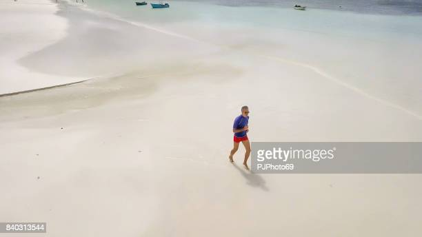 aerial view of man running on tropical beach in seychelles - pjphoto69 stock pictures, royalty-free photos & images