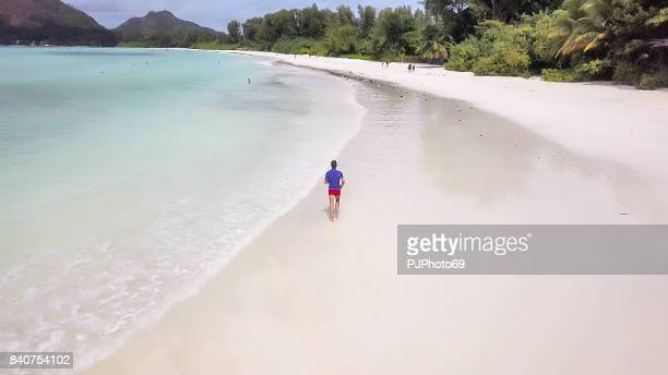 aerial view of man running on tropical beach in seychelles - august stock photos and pictures