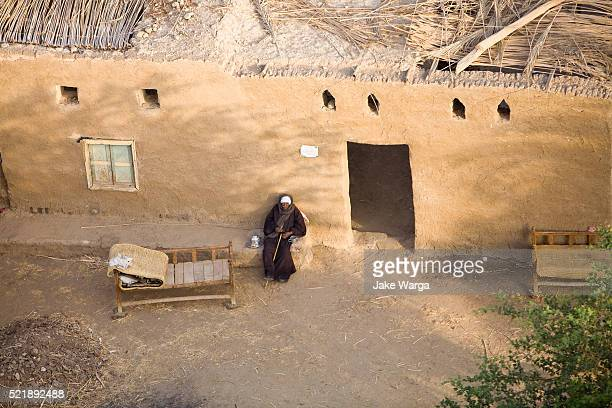 aerial view of man sitting outside his mud thatched house, luxor - jake warga stock pictures, royalty-free photos & images