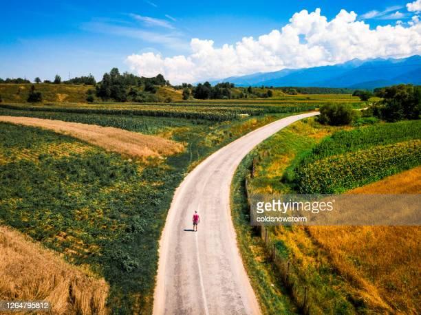 vue aérienne de l'homme marchant seul sur la route sinueuse de campagne - un seul homme photos et images de collection
