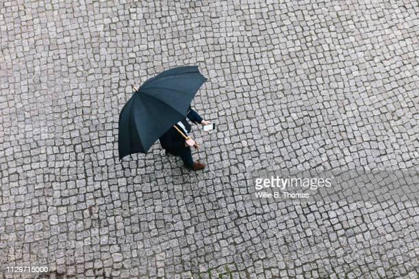 aerial view of man walking with umbrella - laje imagens e fotografias de stock