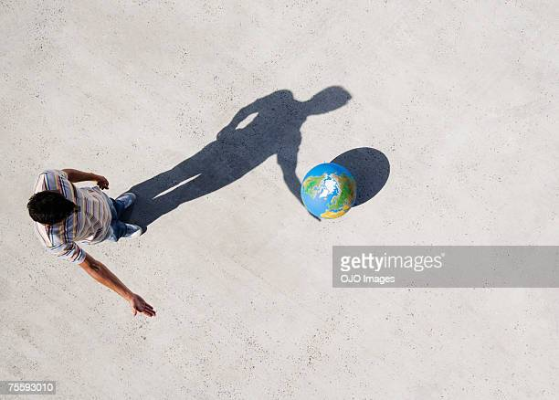 Aerial View of man with shadow and globe