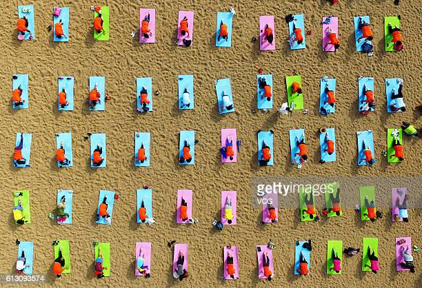 Aerial view of many people practicing yoga on the beach of Wanpingkou Scenic Spot on October 6 2016 in Rizhao Shandong Province of China Wanpingkou...