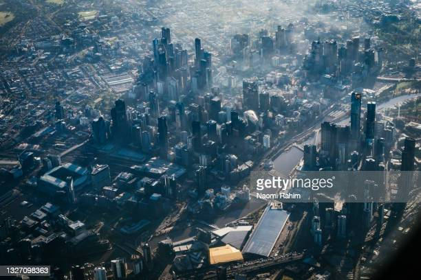 aerial view of melbourne city skyline in fog - docklands stadium melbourne stock pictures, royalty-free photos & images