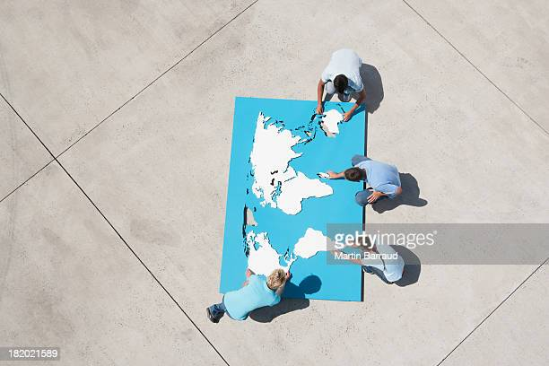 Aerial view of men and women outdoors with world map puzzle