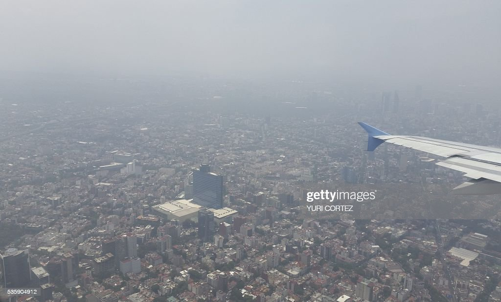 Aerial view of Mexico City covered by alayer of smog on May 30, 2016. Authorities announced recently new measures to combat a recent increase in air pollution in Mexico City, as officials reported an increase in related ailments such as asthma. Ozone levels surged in March, prompting authorities to declare the first air pollution alert in more than a decade and impose extra traffic restrictions that will run until June 30. / AFP / YURI