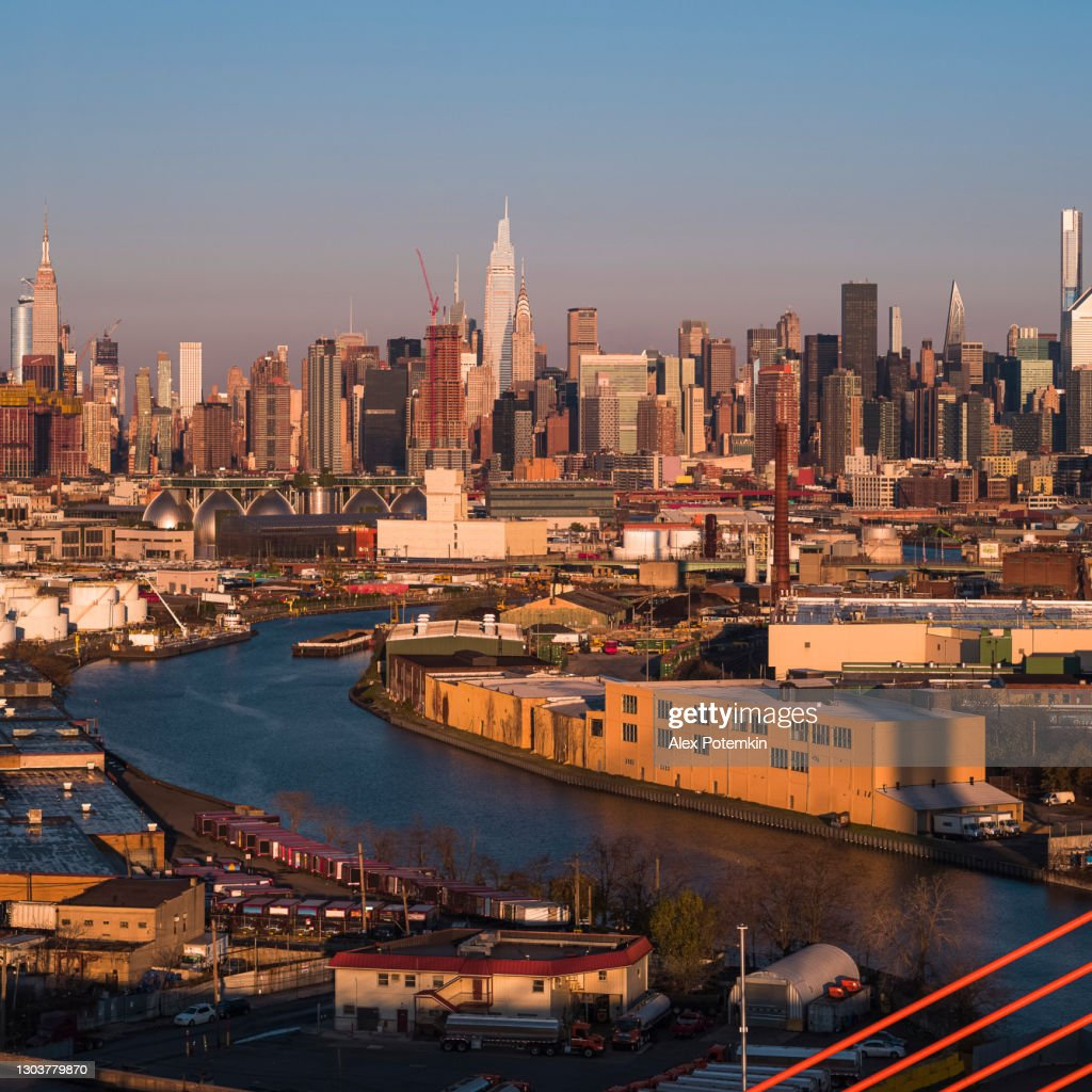 Aerial view of Midtown Manhattan over the industrial district in Williamsburg, Brooklyn, New York, illuminated by sunlight in the early morning. Stitched high-resolution vertical panorama. : Stock Photo
