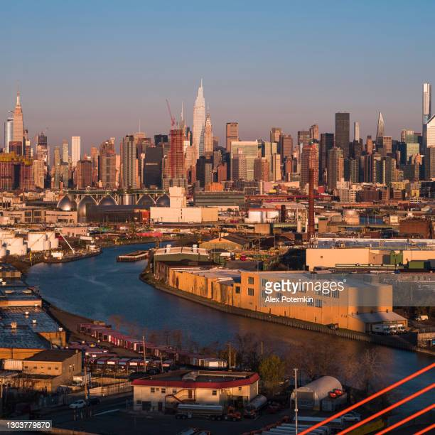 aerial view of midtown manhattan over the industrial district in williamsburg, brooklyn, new york, illuminated by sunlight in the early morning. stitched high-resolution vertical panorama. - brooklyn new york stock pictures, royalty-free photos & images