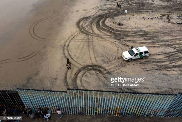 TOPSHOT Aerial view of migrants who form part of the Central American migrant caravan being detained and escorted by a border patrol agent after...