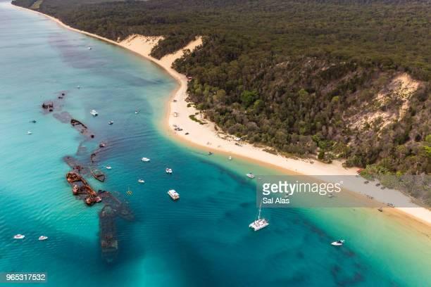 aerial view of moreton island where sea meets forest - baia foto e immagini stock
