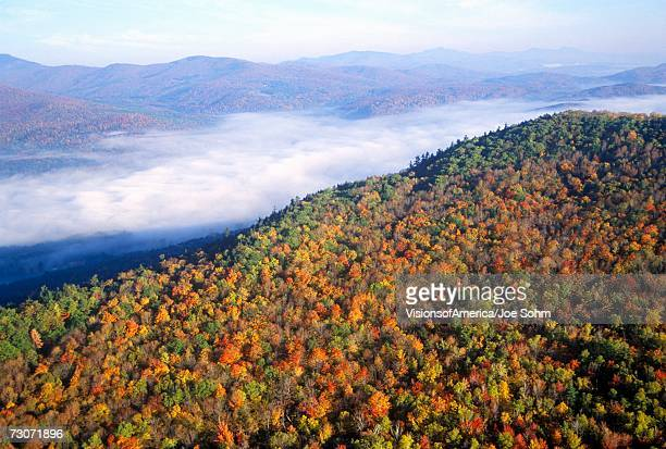 """Aerial view of morning fog over mountains near Stowe, VT in autumn along Scenic Route 100"""