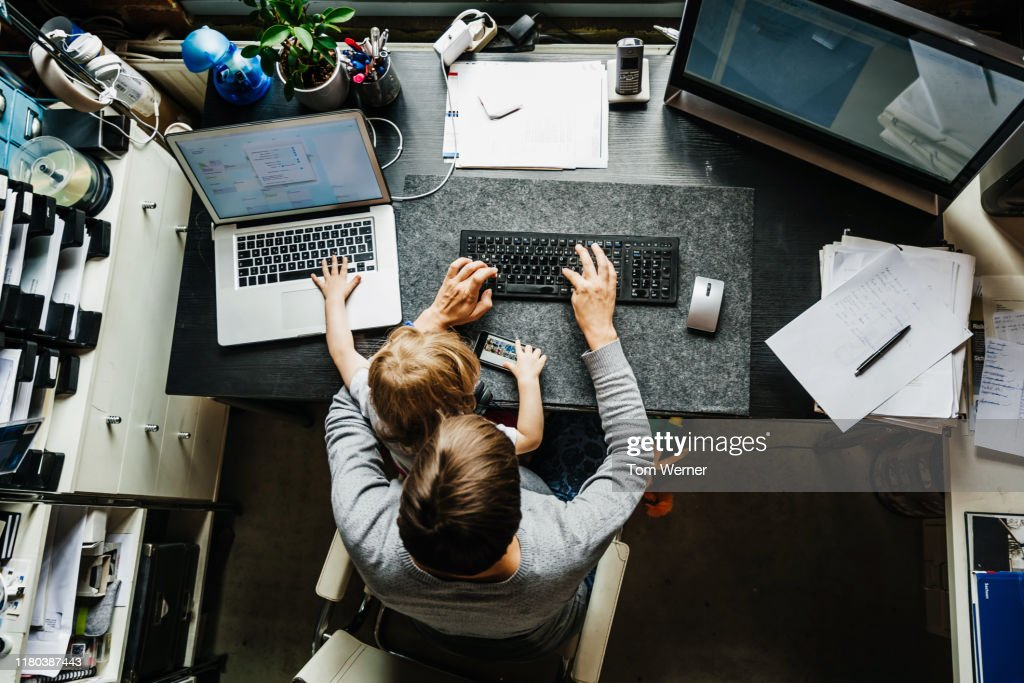Aerial View Of Mother Working In Office At Home With Daughter : Stock Photo