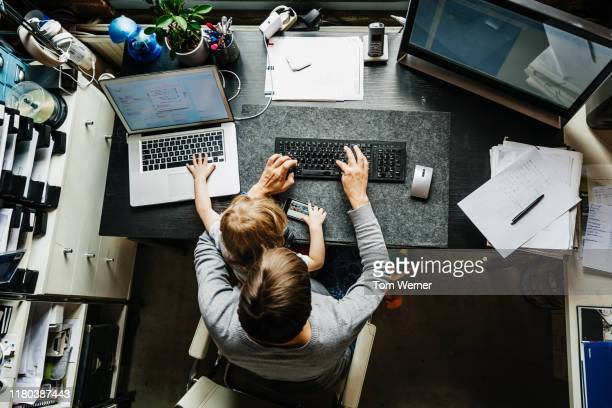 aerial view of mother working in office at home with daughter - working from home stock pictures, royalty-free photos & images