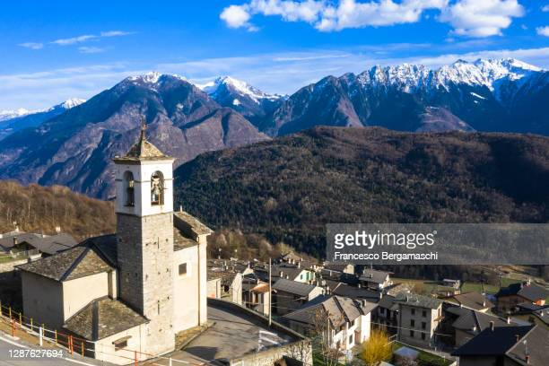 aerial view of mountain village with view on snowcapped mountains. - italia ストックフォトと画像