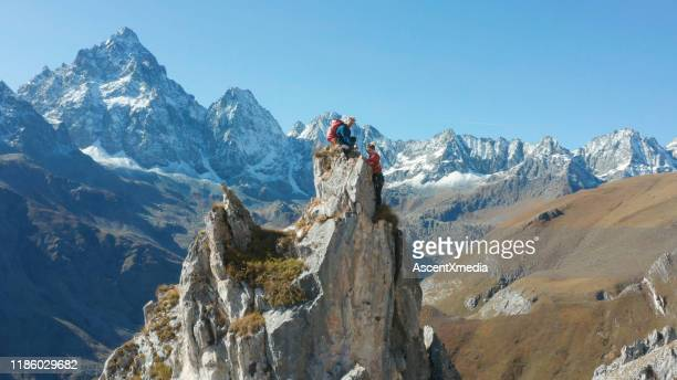 aerial view of mountaineers ascending to pinnacle summit - ascent xmedia stock pictures, royalty-free photos & images