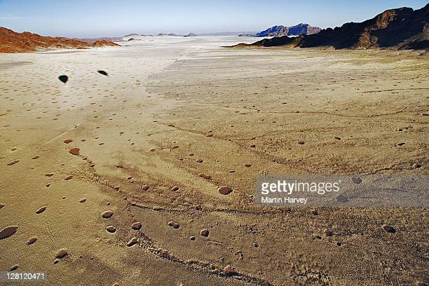 aerial view of mountains near sossusvlei in namib desert. circular patches (aka fairy circles) derived from any vegetation & surrounded by tall grass, cause of this phenomenon is unknown. shadows of two hot-air balloons on grassplain. namib naukluft np, na - light natural phenomenon stock pictures, royalty-free photos & images