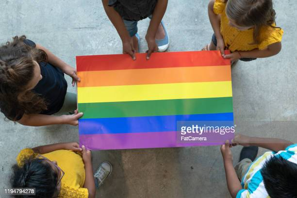 aerial view of multi-ethnic elementary students holding a gay pride poster stock photo - gay rights stock pictures, royalty-free photos & images