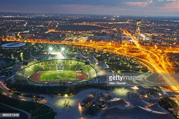 aerial view of munich's olympic stadium illuminated at night - olympiastadion munich stock pictures, royalty-free photos & images