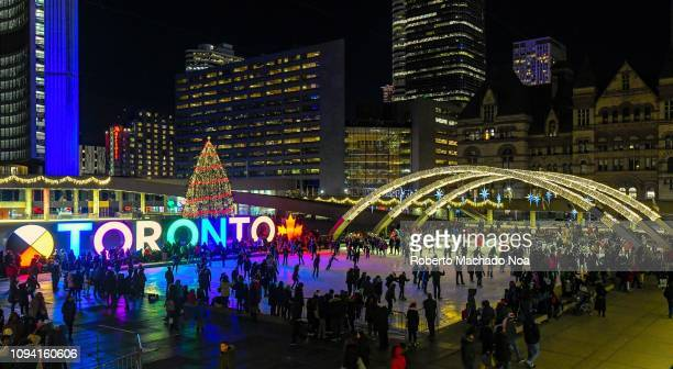 Aerial view of Nathan Phillips Square ice rink during December month. The image shows the Peace Arches, the 3D city sign, and the large Christmas...