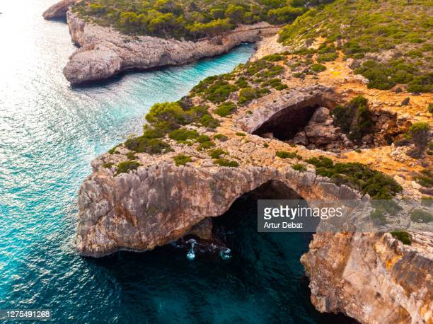 aerial view of natural arch in the beautiful rocky coast of mallorca island. - manacor stock pictures, royalty-free photos & images