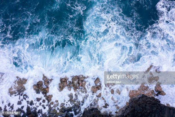 aerial view of ocean waves breaking on rocky beach - riva dell'acqua foto e immagini stock
