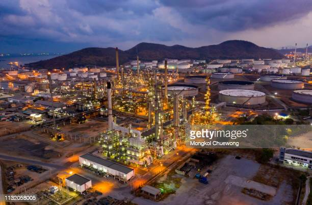 aerial view of oil refinery near international port at night. refinery plant at sunrise. refinery factory and tank - refinery stock pictures, royalty-free photos & images