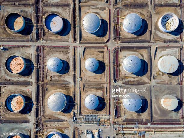 aerial view of oil storage tanks in a grid pattern at torrance. round containers, covered and uncovered. energy infrastructure. - silo stock photos and pictures