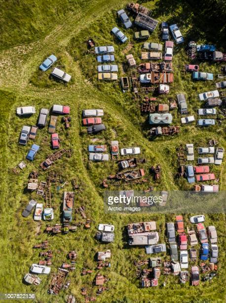 aerial view of old vehicles in the grass - junkyard stock photos and pictures