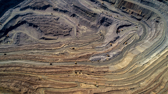 Aerial view of opencast mining quarry with lots of machinery at work. 976995452