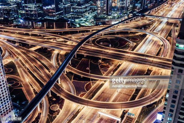aerial view of overpass, metro and city traffic at night - dubai stock pictures, royalty-free photos & images