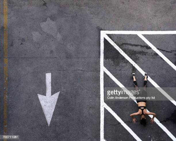 Aerial view of Pacific Islander woman doing push-ups in parking lot