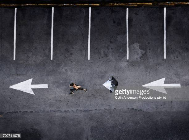 Aerial view of Pacific Islander woman running with parachute in parking lot
