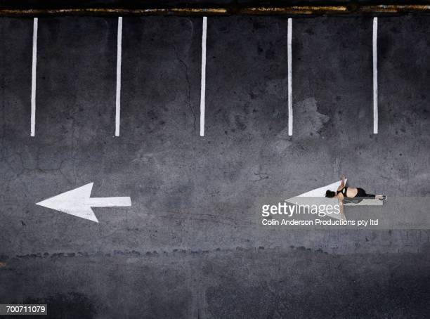 Aerial view of Pacific Islander woman stretching in parking lot