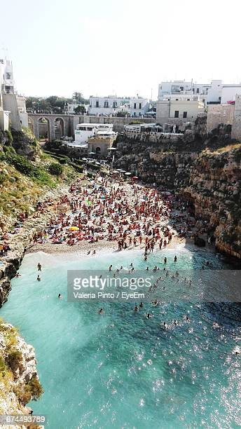 Aerial View Of People At Beach Against Sky In City On Sunny Day
