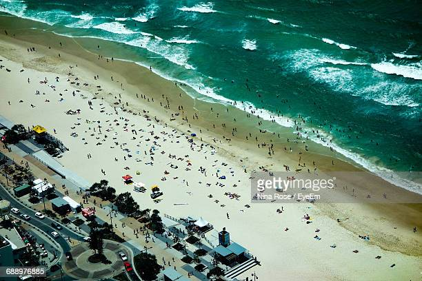 Aerial View Of People At Beach By City