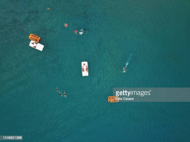 aerial view of people at the beach swimming and having fun on the paddleboat. - pedal boat stock pictures, royalty-free photos & images