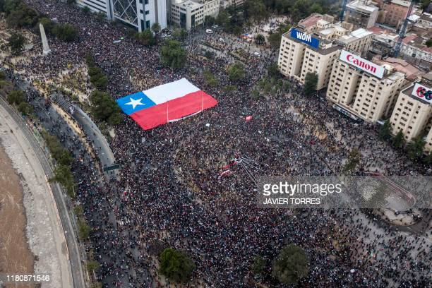 Aerial view of people demonstrating with a giant Chilean national flag against the government of Chilean President Sebastian Pinera in Santiago on...