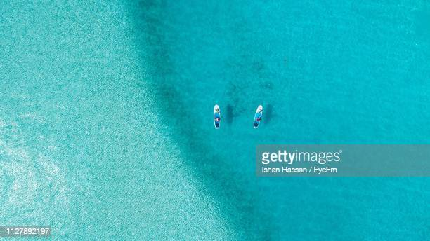 aerial view of people paddleboarding in sea - turquoise colored stock pictures, royalty-free photos & images