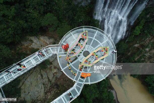 Aerial view of people performing dragon dance on a glass bridge featuring a circular observation deck along a cliff at the Gulongxia scenic spot on...