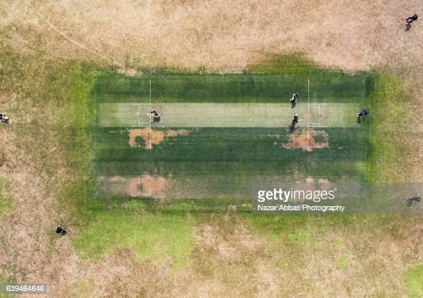 aerial view of people playing cricket in ground. - cricket pitch stock pictures, royalty-free photos & images