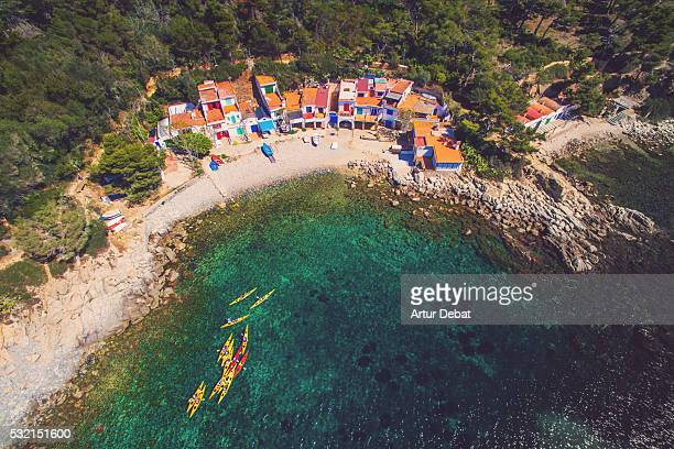 Aerial view of people practicing kayak in the Mediterranean Costa Brava shoreline with green waters on summertime with fisherman town on the beach.